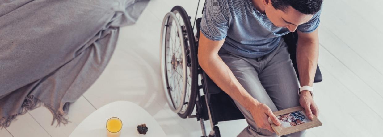 Man in een rolstoel kijkt naar een foto
